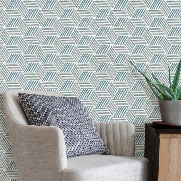 beige chair with blue and green geometric wallpaper