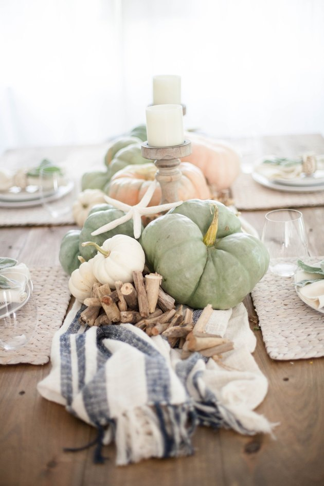 A centerpiece with seashells and pumpkins
