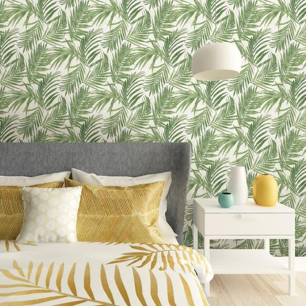 bedroom with yellow bedding and green vines wallpaper