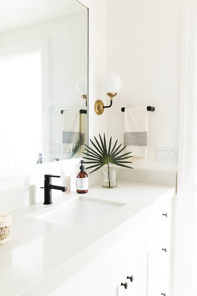 undermount bathroom sink with white cabinets and black hardware