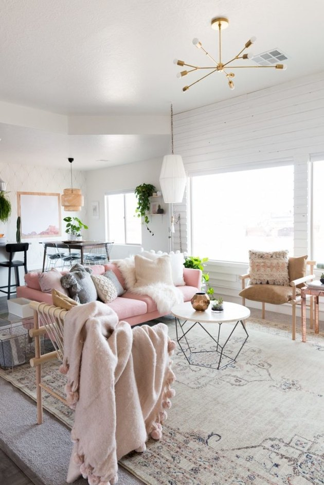 white living room with pink sofa and large area rug