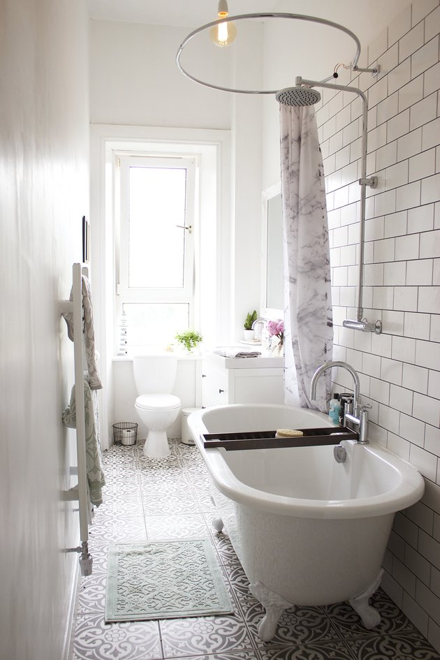 white bathroom with subway tile accent wall and clawfoot bathtub