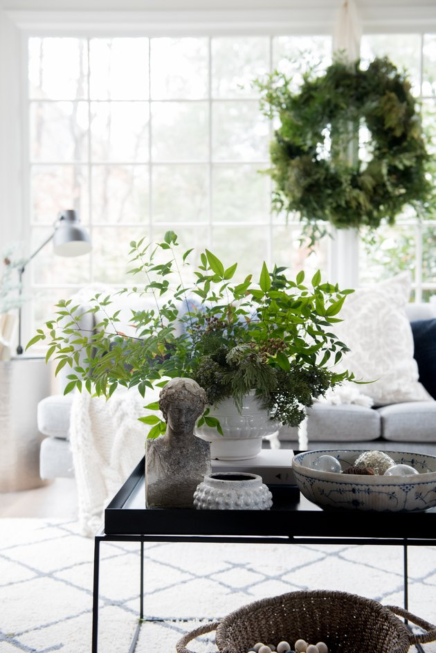 White sunroom with winter greens in vase and wreath hanging on windows