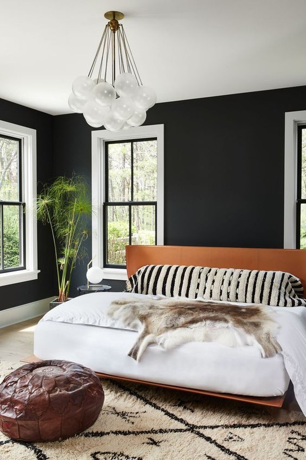 bedroom with black walls and platform bed
