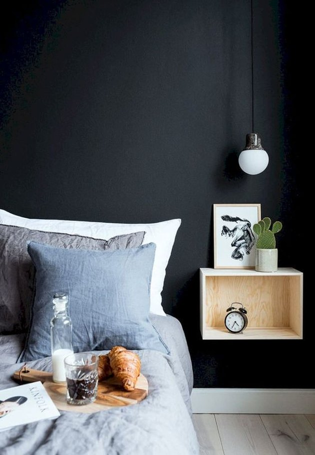 bedroom with black walls and floating nightstand