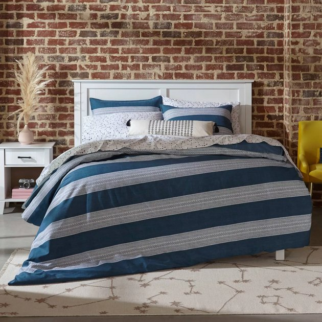 bed with blue sheets near brick wall