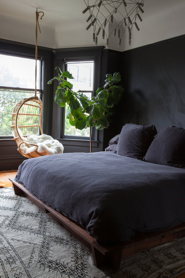 bedroom with matte black walls and black bedding with hanging chair in the window