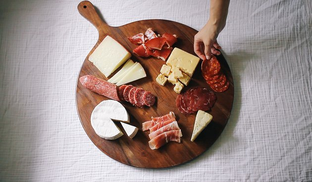 Placing the meat and cheese on the board