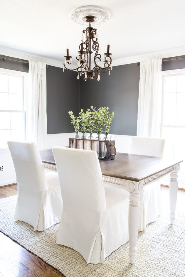 gray dining room with white wainscoting and slipcovered chairs