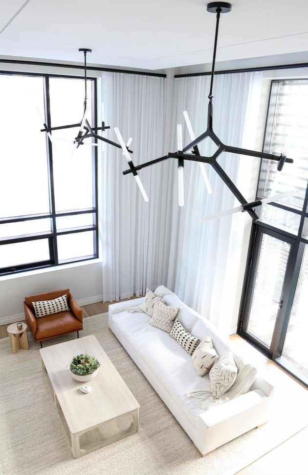 Contemporary chandeliers hung high as a pair.