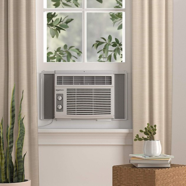 air conditioning unit on window near plant and books