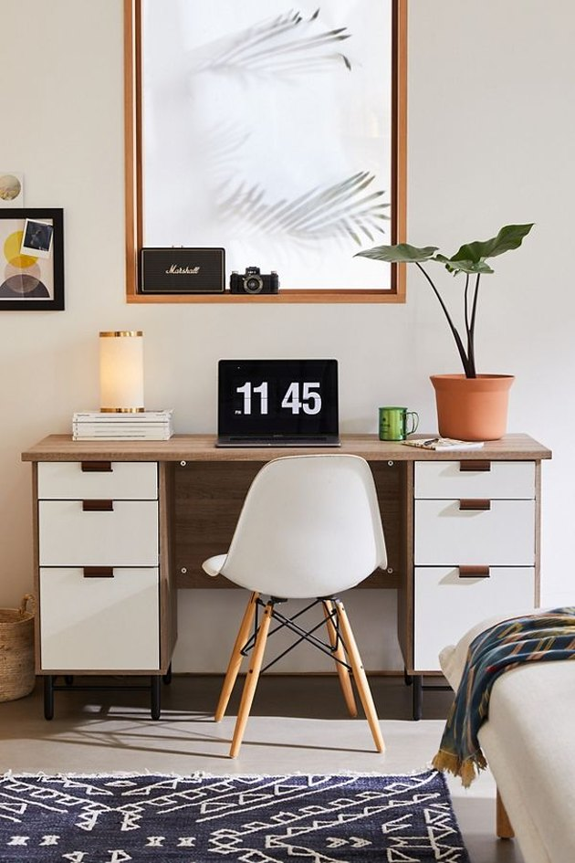 desk with plant and art print and white chair