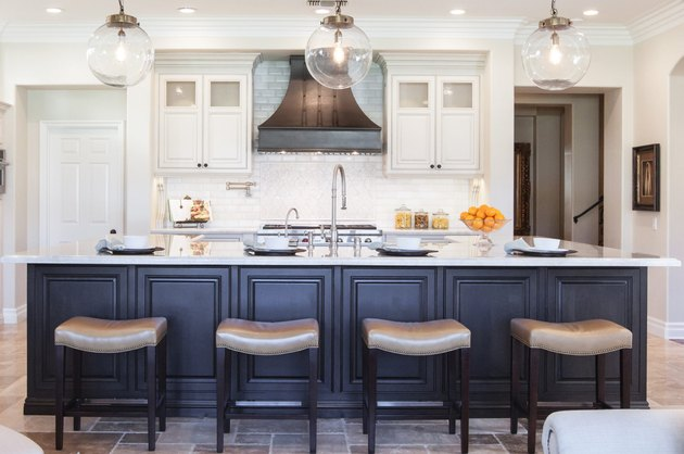 brown travertine kitchen flooring with blue island and white cabinets