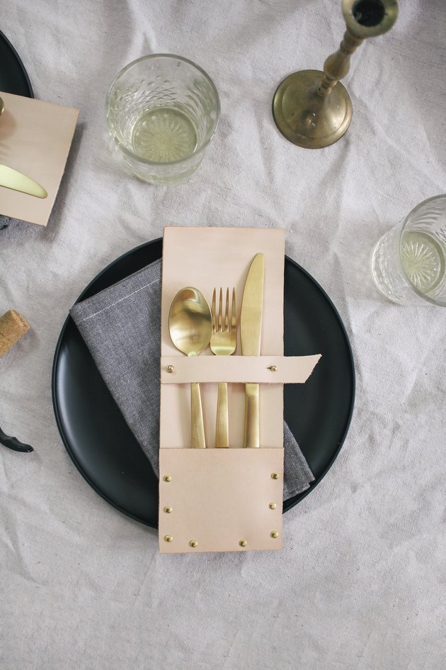 leather and brass studded flatware pack on a black plate with napkin