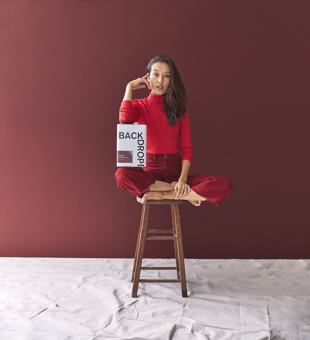 woman posing with paint near a dark red wall