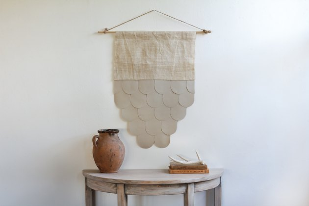 Leather and burlap wall hanging over wood table.
