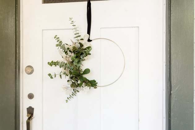 wreath with eucalyptus and gold hoop hanging from front door