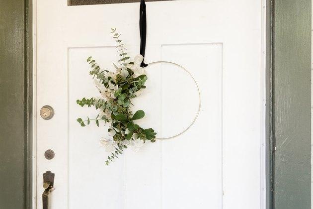 wreath with eucalyptus and gold hoop hanging from front door