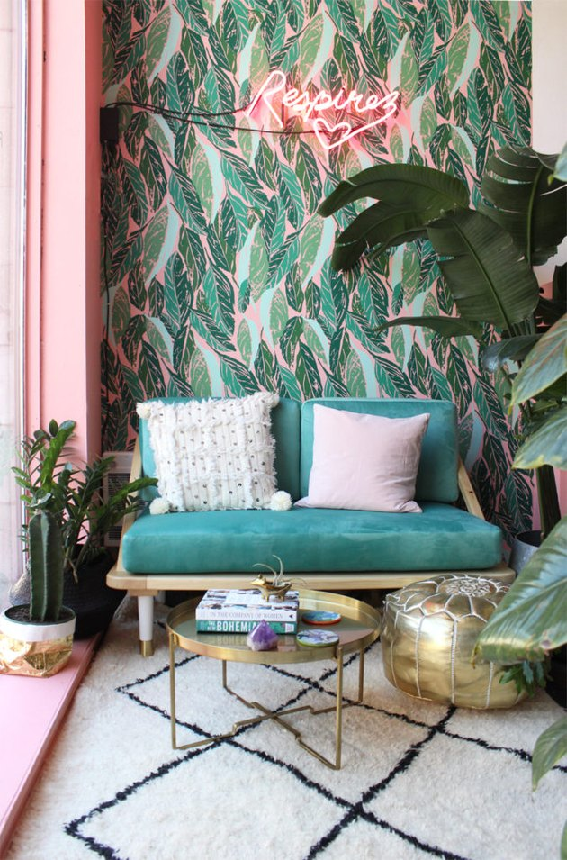 tropical living room with neon sign and palm leaf wallpaper