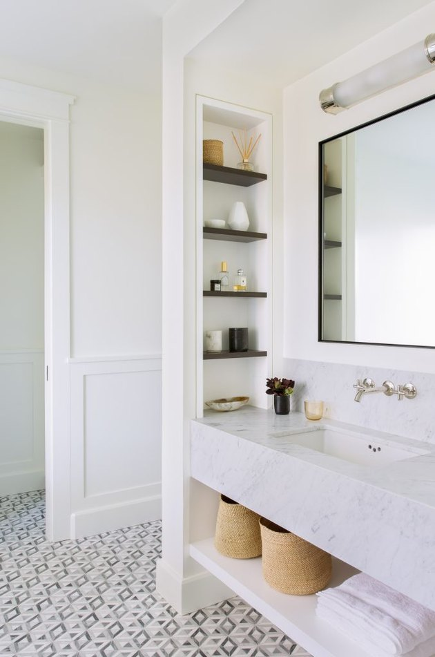 bathroom storage idea with built-in niches and towel storage under sink