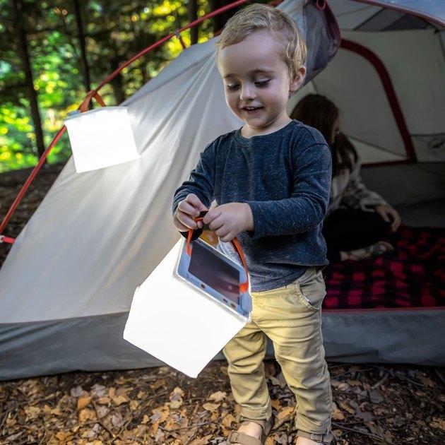 child holding a LuminAid lamp