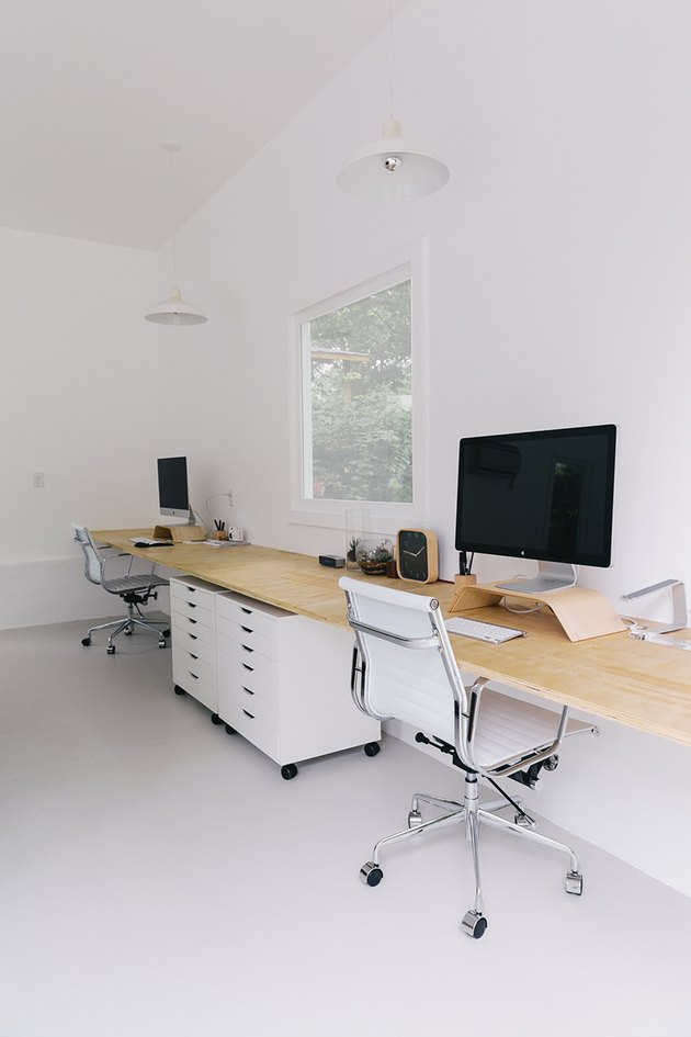 Home Office Organization Ideas with Two office chairs at work station with natural wood desk, white file cabinets on wheels.