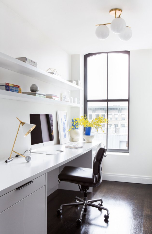 Home Office Organization Ideas with White desk, black desk chair, brass desk lamp, white shelves, white globe light.