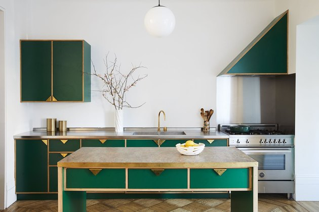 modern kitchen island with green cabinets and brass pulls