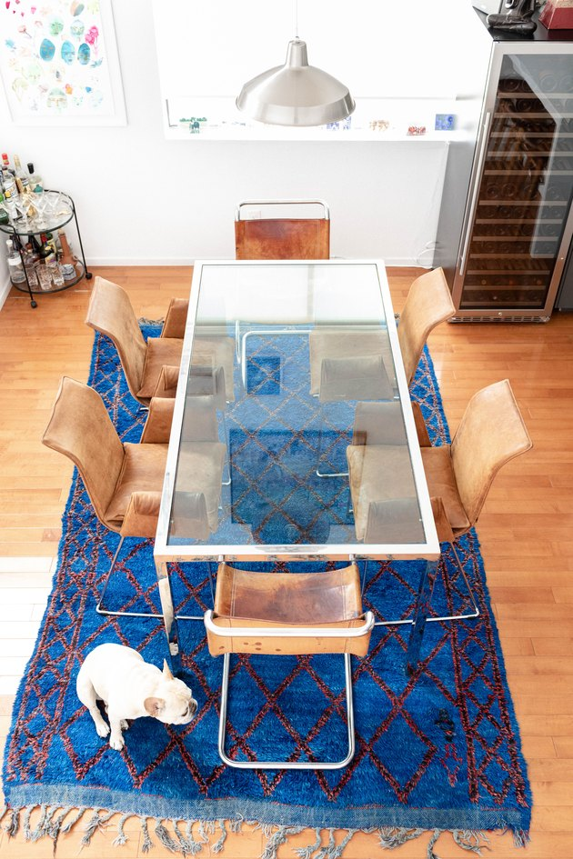 Glass dining room table with blue rug