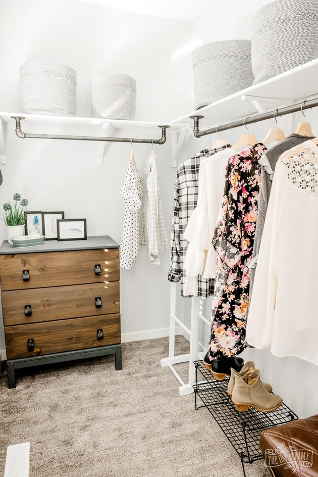 Farmhouse industrial pipe closet idea with white walls and wood dresser