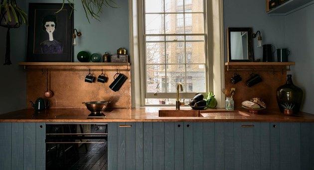 blue kitchen with copper backsplash