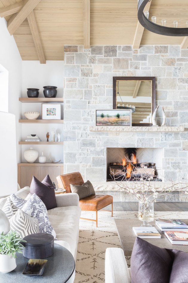 farmhouse living room with stone wall fireplace and open shelving