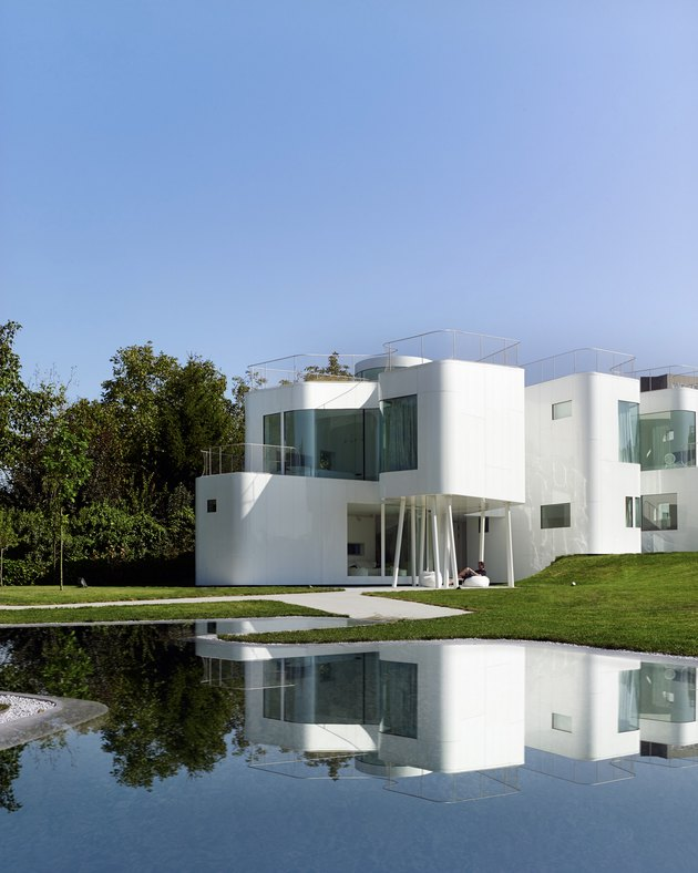 Bauhaus style residence with white exterior and large windows next to pond