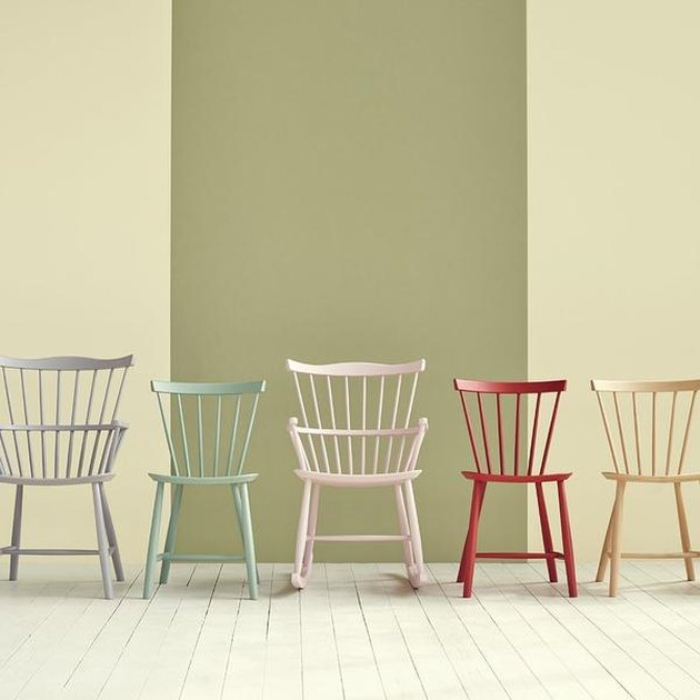 row of chairs in different colors with striped wall in the background