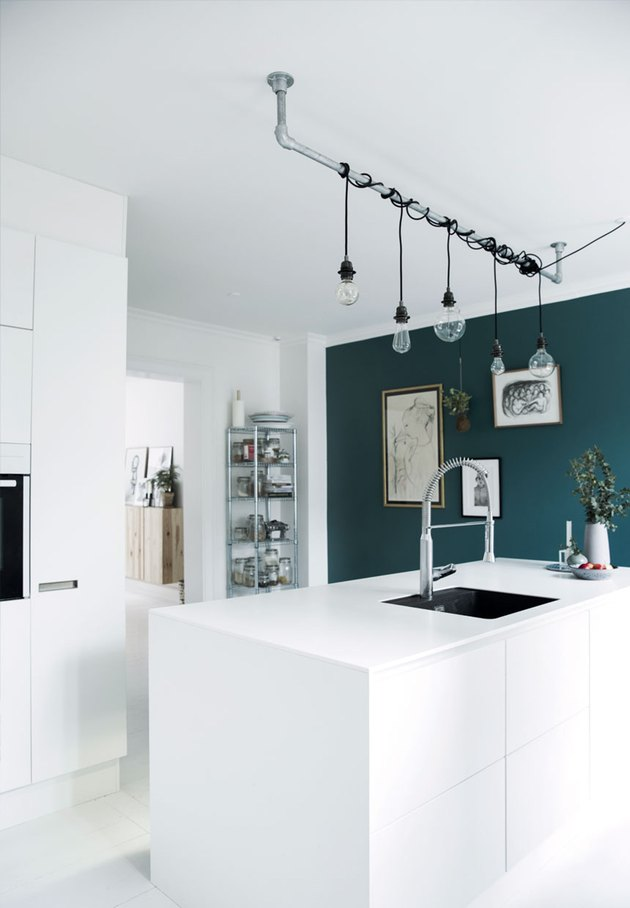 green kitchen accent wall with white cabinets and industrial lighting over island