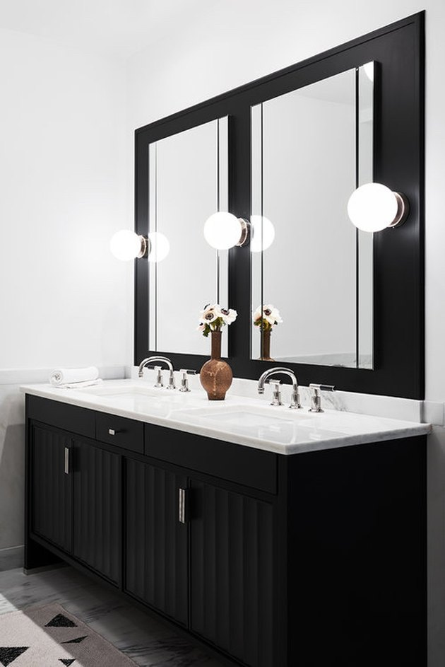 bathroom lighting idea with wall sconces and black vanity cabinet
