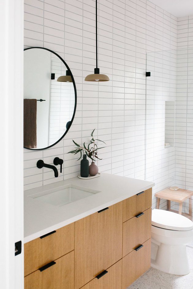 white subway tile in bathroom with minimalist bathroom storage and black faucet