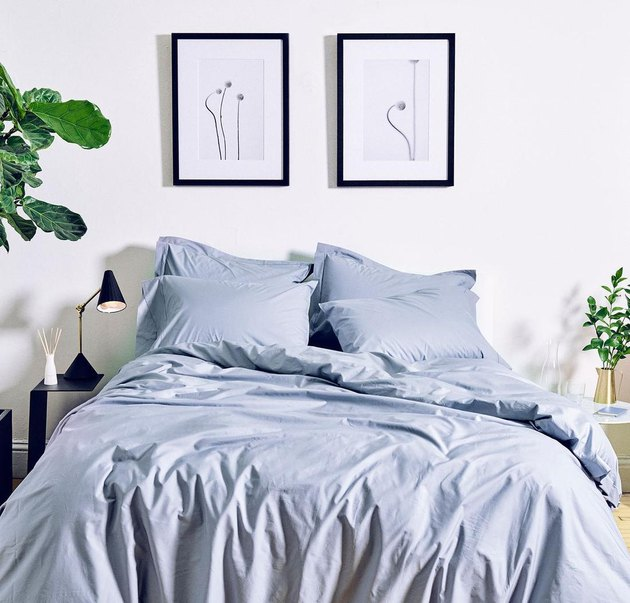 bedroom with blue sheets and artwork on the wall