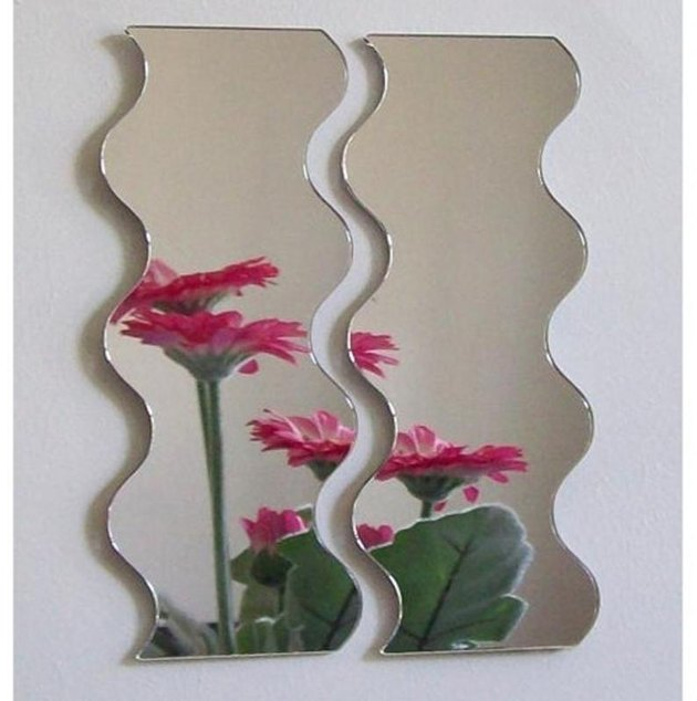 pair of wavy mirrors with flowers reflected