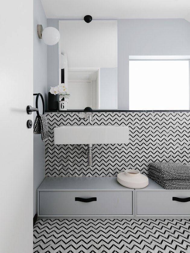 Scandinavian bathroom with black and white patterned tile and wall mounted sink