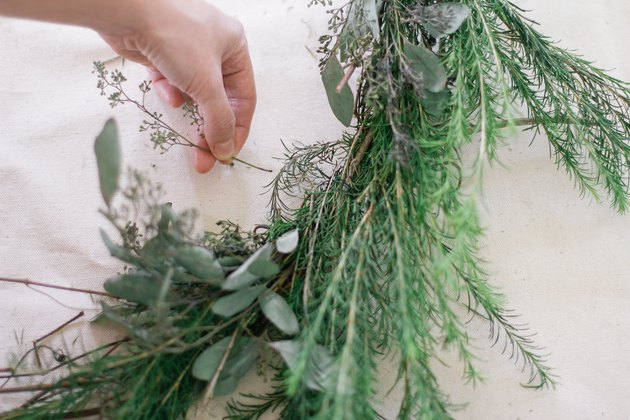 Tucking sprig of eucalyptus into wreath