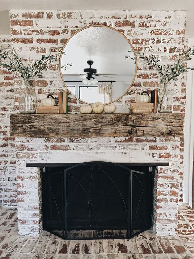 fall-inspired mantel decor against rustic whitewashed brick wall