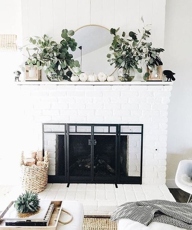 fall-inspired modern mantel decor with white pumpkins and greenery