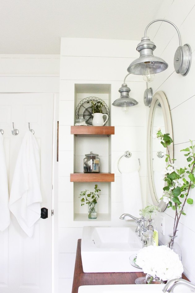 Rustic accents on wooden shelves in a white bathroom