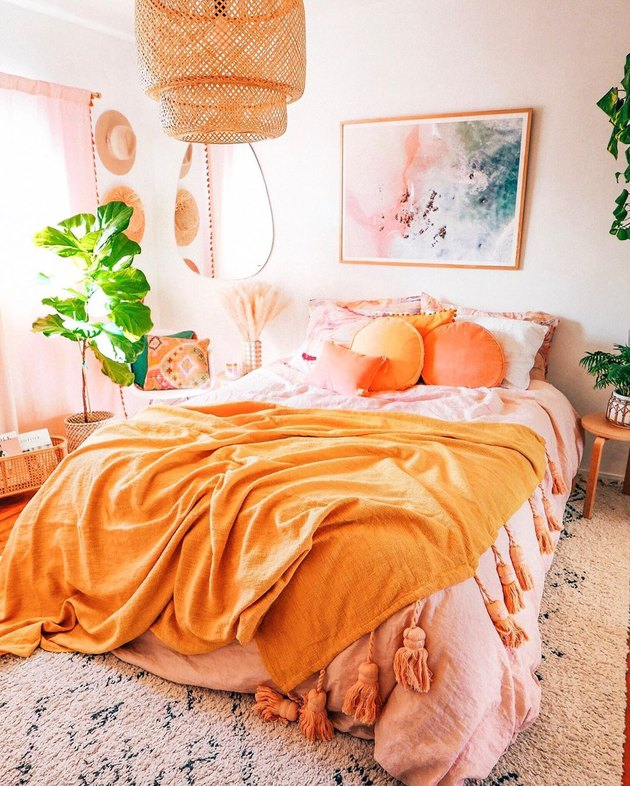 Warm colors in bedroom with pink and orange palette and  bamboo pendant light and boho decor