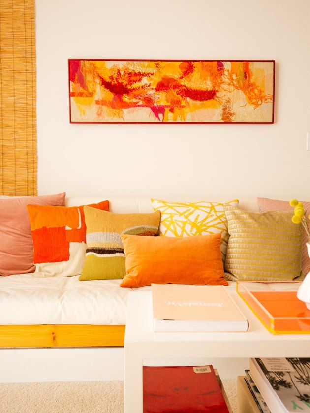 warm colors with orange and yellow in living room with abstract painting and throw pillows