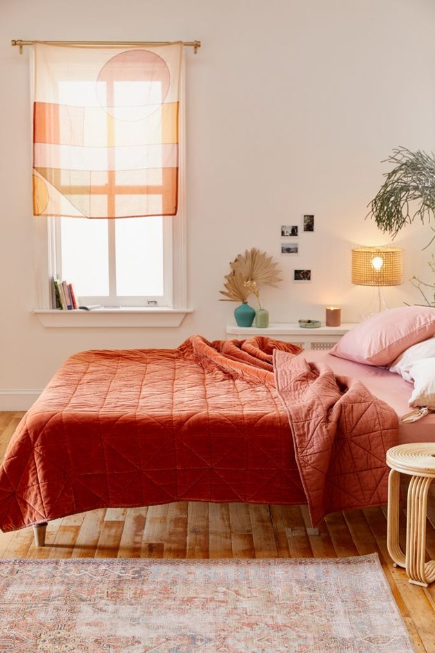 Warm colors in bedroom with rust-colored quilt and wall hanging over window