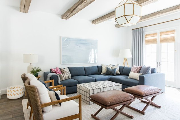 farmhouse family room idea with blue sectional and wood ceiling beams