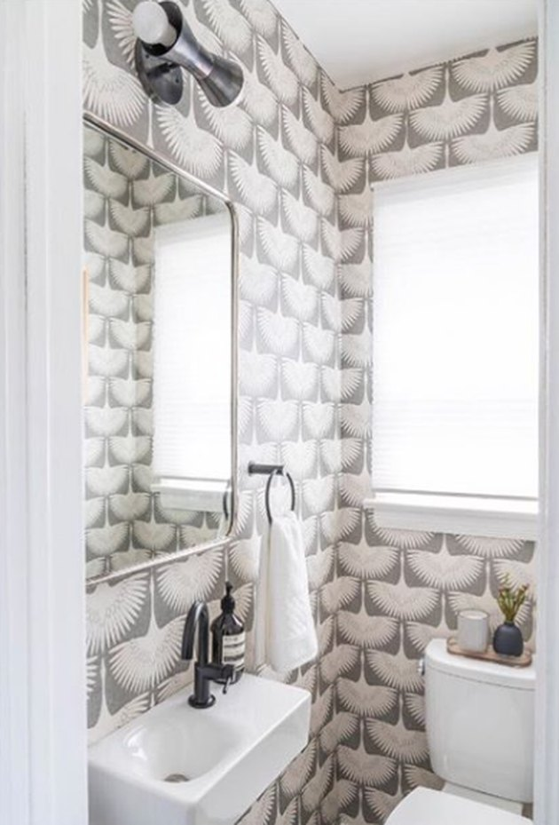 bathroom idea with removable wallpaper and wall-mounted sink next to window and toilet