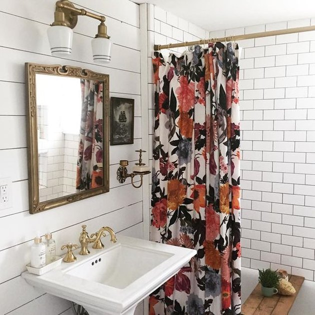 white bathroom with floral shower curtain and pedestal sink